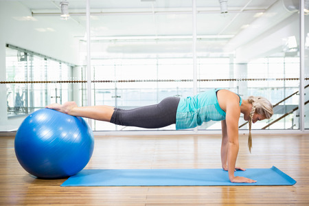 planking: Fit blonde planking on mat with exercise ball in fitness studio