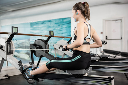 body toning: Fit brunette on drawing machine at the gym Stock Photo