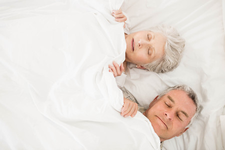Senior couple sleeping in bed under blanket Stock Photo