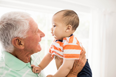 multi family house: Senior man playing with his grandson at home Stock Photo