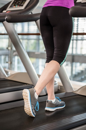 lower section: Lower section of fit woman on treadmill at the gym