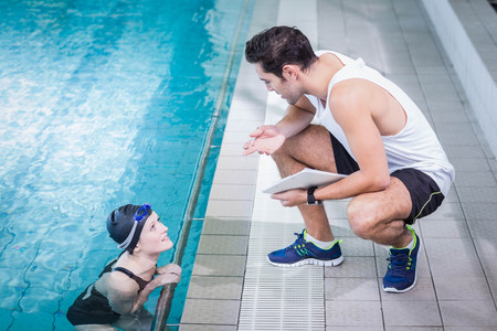 water sport: Fit trainer talking to swimmer in leisure center