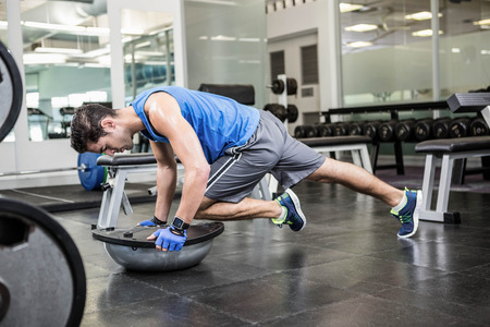 standing up: Muscular man exercising with bosu ball in the gym Stock Photo
