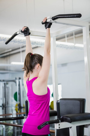 pull up: Fit woman doing pull up at the gym Stock Photo