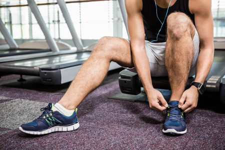 lower section: Lower section of man sitting on treadmill and tying the shoelace at the gym
