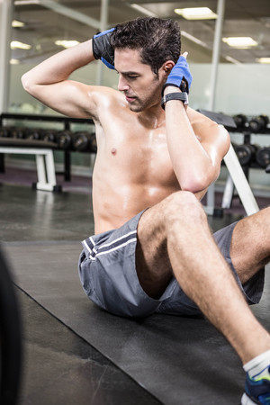 sitting up: Shirtless man doing sitting up in the gym