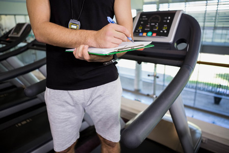 adult  body writing: Mid section of man on treadmill writing on clipboard at the gym Stock Photo