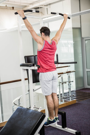 pull up: Muscular man doing pull up in a gym