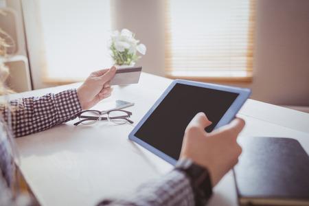 Zakenvrouw met behulp van haar creditcard om online te kopen op haar bureau in het kantoor