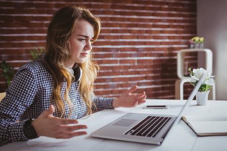 misunderstanding: Young hipster businesswoman misunderstanding her laptop at her desk in office