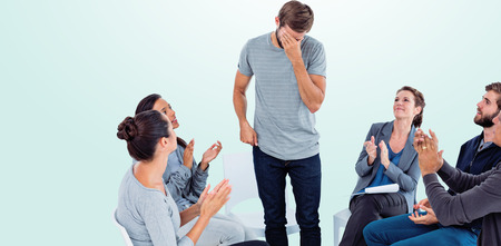applauding: Rehab group applauding delighted man standing up against blue background Stock Photo