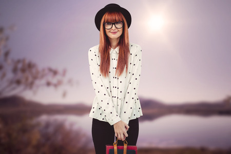 beautiful bangs: Smiling hipster woman holding book belt against wooden background