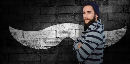 hooded shirt: Portrait of confident hipster with hooded shirt against texture of bricks wall