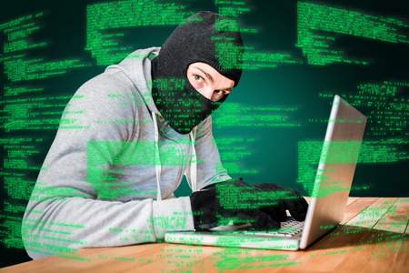 thievery: Focused thief with hood typing on laptop against green background with vignette