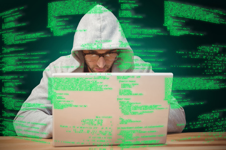 hooded shirt: Creative businessman with hooded shirt working on laptop against green background with vignette Stock Photo