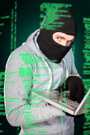 robbing: Focused thief with hood typing on laptop against green background with vignette