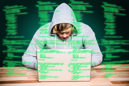 thievery: Man in hood jacket hacking a laptop against green background with vignette Man in hood jacket hacking a laptop on black background Stock Photo