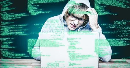 Man in hood jacket hacking a laptop against green background with vignette Man in hood jacket hacking a laptop on black background Stock Photo
