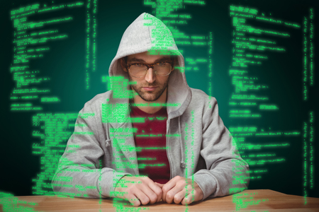 hooded shirt: Thoughtful man with hooded shirt sitting at desk against green background with vignette