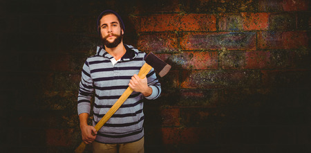 hooded shirt: Portrait of confident hipster with hooded shirt holding axe against texture of bricks wall
