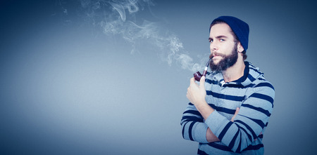 smoking pipe: Portrait of serious hipster smoking pipe against grey vignette Stock Photo
