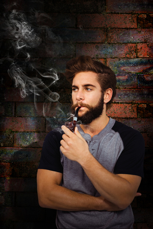 smoking pipe: Confident hipster smoking pipe against texture of bricks wall