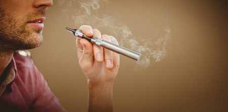 artistic addiction: Cropped image of man smoking electronic cigarette against grey background with vignette