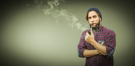 smoking pipe: Hipster wearing knitted hat smoking pipe against grey vignette