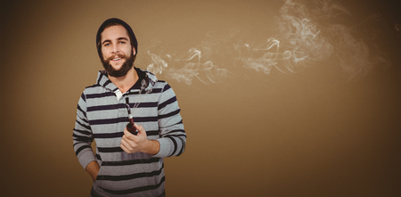 hooded shirt: Happy hipster with hooded shirt holding smoking pipe against grey background with vignette Stock Photo