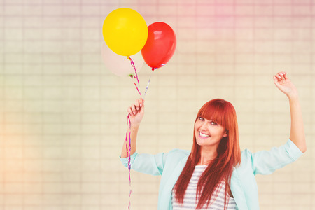 beautiful bangs: Smiling hipster woman holding balloons against textured background Stock Photo