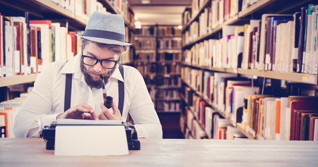 smoking pipe: Hipster smoking pipe while working at desk against close up of a bookshelf