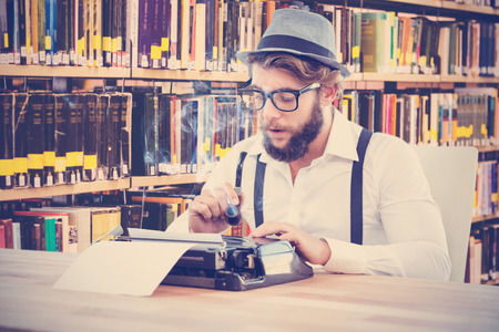 Hipster Holding Smoking Pipe While Working On Typewriter Against Close Up Of A Bookshelf Stock Photo