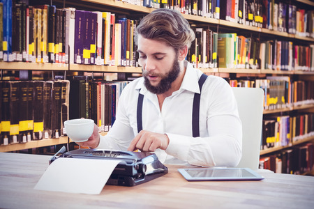 Hipster Holding Coffee Working On Typewriter Against Close Up Of A Bookshelf Stock Photo