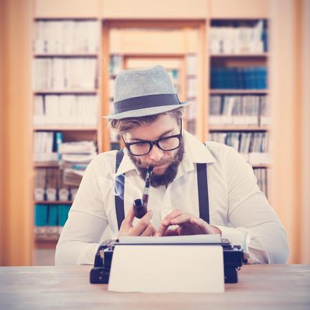 Hipster kouří dýmku při práci u stolu proti knihovně