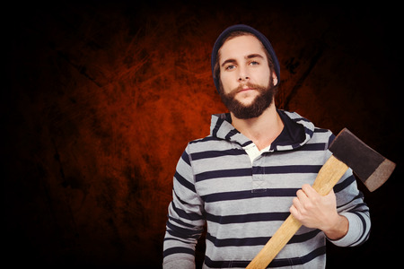 hooded shirt: Portrait of confident hipster with hooded shirt holding axe against shades of brown Stock Photo