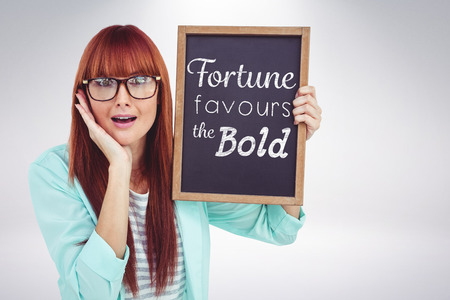 favours: Smiling hipster woman holding blackboard against grey background