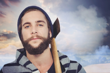 hooded shirt: Close-up portrait of hipster with hooded shirt holding axe against country scene Stock Photo