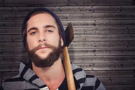 hooded shirt: Close-up portrait of hipster with hooded shirt holding axe against wooden background Stock Photo
