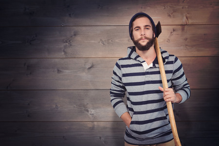 hooded shirt: Portrait of hipster with hooded shirt holding axe against bleached wooden planks background