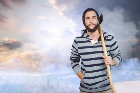 hooded shirt: Portrait of hipster with hooded shirt holding axe against country scene Stock Photo