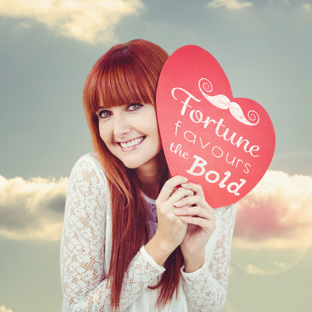favours: Smiling hipster woman with a big red heart against bright blue sky with cloud