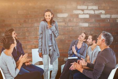 circulo de personas: Rehab grupo aplaudiendo mujer encantada de pie contra la pared de ladrillo