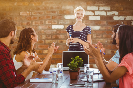 manos aplaudiendo: Colleagues clapping hands in a meeting against brick wall Foto de archivo