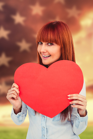 rippling: Attractive hipster woman behind a red heart against american flag rippling over grassy landscape