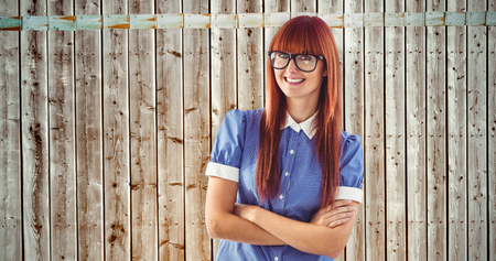 pale wood: Attractive hipster woman with crossed arms against wooden background in pale wood