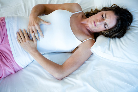 clutching: tiredwoman lying in her  bed clutching her stomach Stock Photo