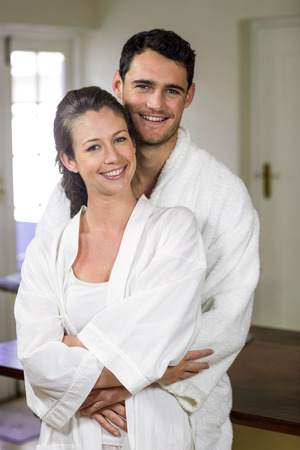 each other: Portrait of couple in bathrobe smiling while embracing each other in kitchen