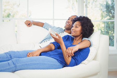 changing channel: Happy couple lying on the sofa holding remote in the living room Stock Photo