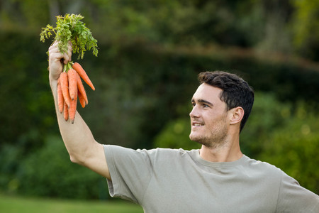 plucked: Young man holding bunch of freshly plucked carrots and smiling