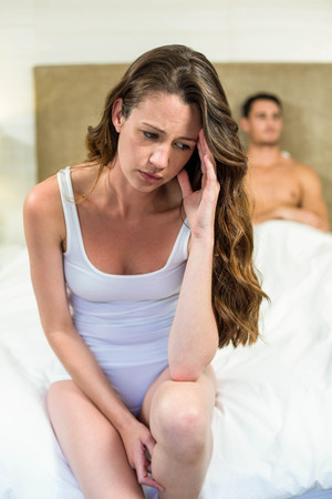 Upset couple sitting on after having an argument Stock Photo